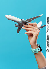Image of hand with airplane on empty blue background