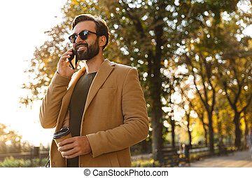 Image of handsome adult man talking on smartphone while walking in park
