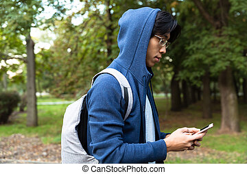 Image of handsome asian guy in casual wear and eyeglasses using cell phone, while walking through green park