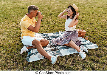 Image of handsome middle-aged man taking photo of nice woman on retro camera while sitting in park