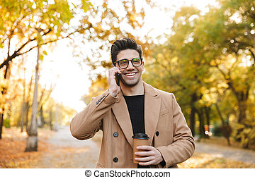 Image of handsome young man wearing coat talking on smartphone and smiling in autumn park