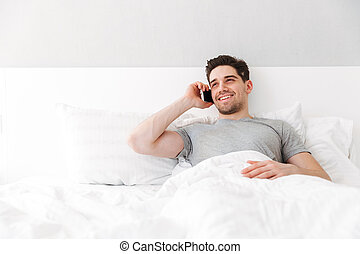 Image of happy awake man in t-shirt smiling while lying alone in bed with white linen, and having pleasant mobile call