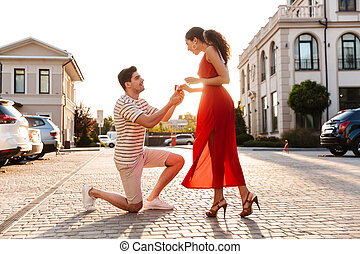 Image of happy bristle man making marriage proposal to his girlfriend