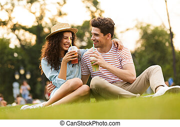 Image of happy couple man and woman 20s sitting on green grass in park, and drinking beverages from plastic cups