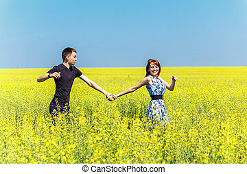Image of happy couple running in yellow meadow