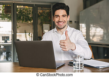 Image of happy office guy 30s wearing white shirt laughing and showing thumb up at camera, while sitting and working on laptop