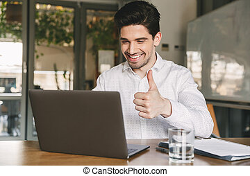 Image of happy office guy 30s wearing white shirt laughing and showing thumb up at laptop, during video conference or call
