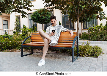 Image of happy young man using smartphone and smiling while sitting