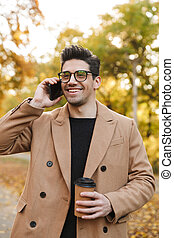 Image of happy young man wearing coat talking on smartphone and smiling in autumn park