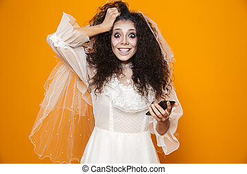 Image of happy zombie woman on halloween wearing wedding dress and holiday makeup using cell phone, isolated over yellow background