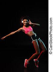 Image of joyful african american woman in headphones dancing and smiling