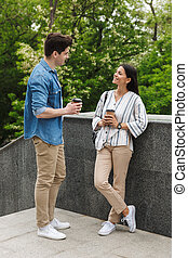 Image of joyful couple smiling and talking while standing on stairs outdoors