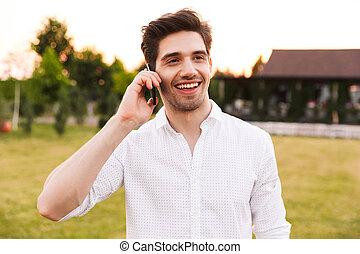 Image of joyful young man 25-30 wearing white shirt smiling,...