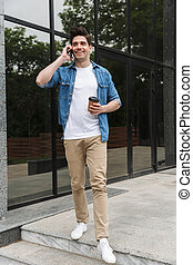 Image of joyful young man drinking takeaway coffee and talking on cellphone while standing over building