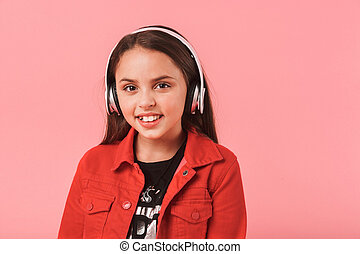 Image of joyous little girl in casual wearing headphones listening to music, isolated over red background
