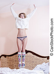image of jumping high beautiful blond young woman sexy girl having fun happy smiling & looking at camera on white bed background