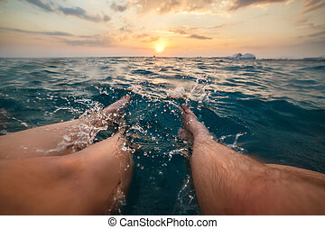 Image of legs of two people splashing aquamarine sea water on sunset