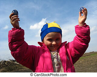 little girl with Easter eggs on a background of the blue sky