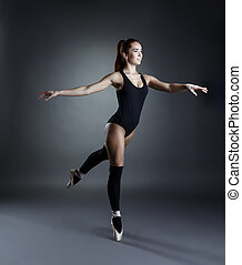 Image of lovely ballerina dancing in studio