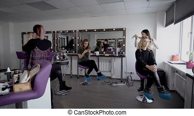 Image of luxury beauty parlour. Three models are sitting in the hall and two professional experts are working together to create images for clients and preparing them for photography.