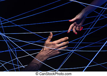 Image of male and female hand among threads in neon light