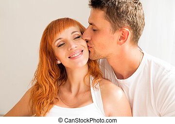 man kisses his woman on the cheek