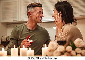 Image of man making proposal to his girlfriend during romantic dinner