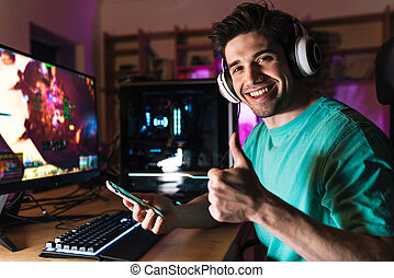 Image of man showing thumb up and using cellphone while playing game