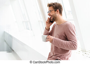 Image of man talking on smartphone while standing over window indoors