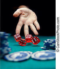 Image of man throwing red dice on table with chips in casino