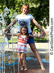 mother and daughter dancing in the fountains
