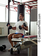 Image of muscular man exercising in gym
