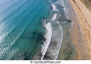 ocean waves, sandy beach with people bathing in the water, view from drone, Lanzada beach, Galicia, Spain