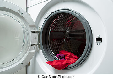 Image of open washing machine with red cloth, close-up