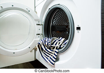 Image of open washing machine with striped cloth, close-up