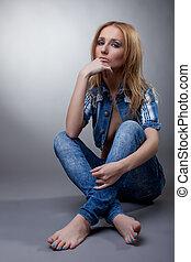 Image of pensive model posing in denim suit