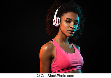 Image of pleased african american woman in headphones looking at camera