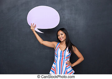 Image of pleased asian woman 30s holding blank thought bubble above her head with copyspace for your text, standing isolated over gray background