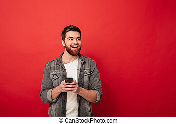 Image of Pleased bearded man holding smartphone and looking away