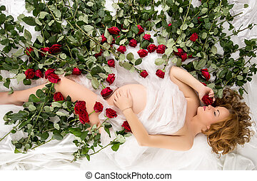 Image of pregnant woman posing in bed with roses