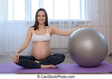 image of pregnant woman sitting on the floor with fitball