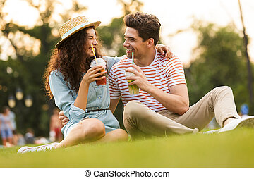 Image of pretty couple man and woman 20s sitting on green grass in park, and drinking beverages from plastic cups