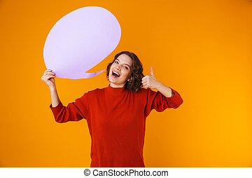 Image of pretty girl holding thought bubble with copyspace while standing isolated over yellow background