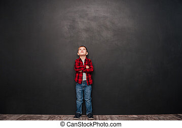 Image of pretty little boy standing over chalkboard