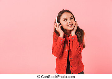 Image of pretty little girl in casual wearing headphones listening to music, isolated over red background