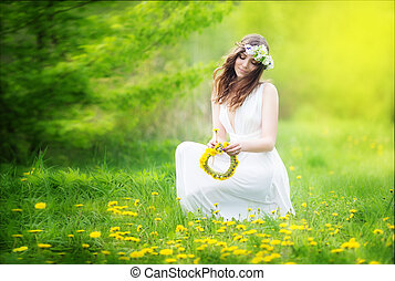 Image of pretty woman in a white dress weaves garland from ...