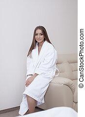 Image of pretty woman in bathrobe sitting on sofa