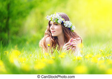 Image of pretty woman lying down on dandelions field, happy cheerful girl resting on dandelions meadow, relaxation outdoor in springtime, vacation