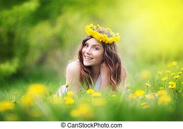 Image of pretty woman lying down on dandelions field, happy...