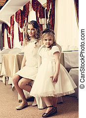 Image of pretty young sisters posing in restaurant